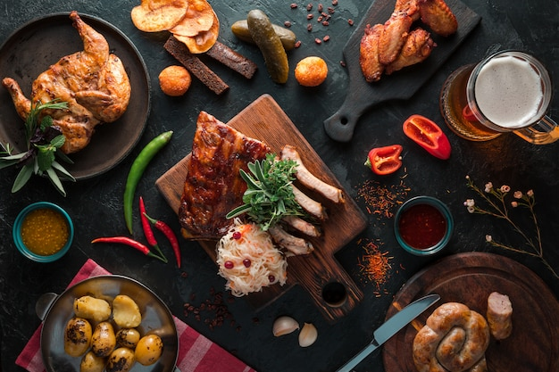 Costine di maiale barbecue con salsiccia, pollo e patate su uno sfondo nero ardesia con boccale di birra. vista dall'alto