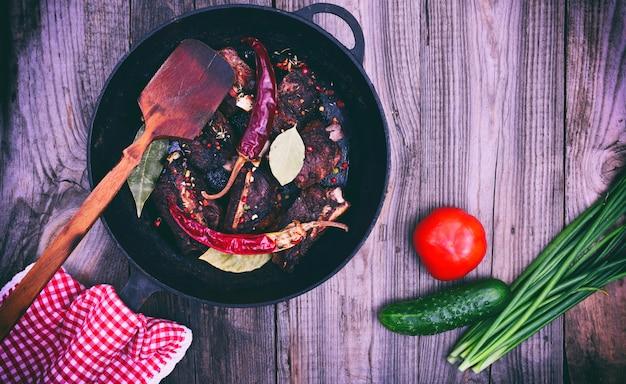 Costine di maiale con spezie in una padella nera