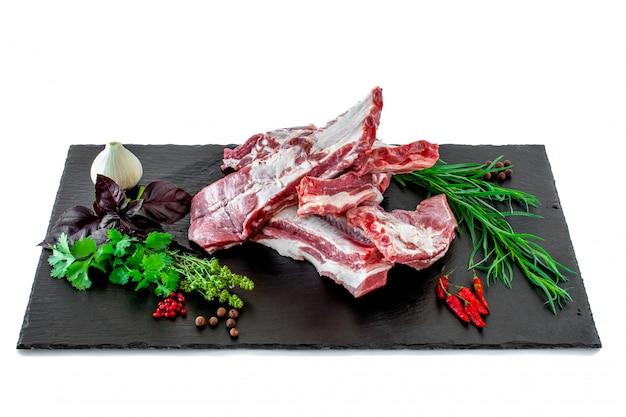 Costine di maiale crude con erbe fresche su un tagliere di pietra scura.