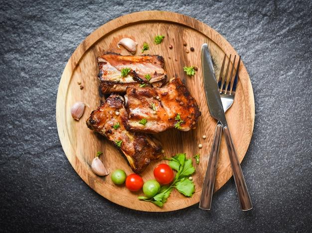 Costine di maiale grigliate alla griglia con erbe e spezie pomodori sul vassoio in legno