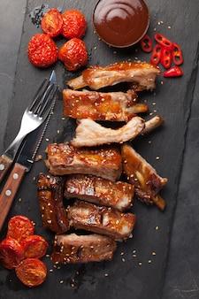 Costine di maiale in salsa barbecue e pomodori arrostiti al miele.