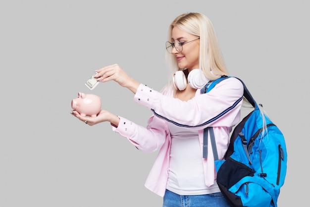 Costo dell'istruzione universitaria. donna sollecitata ritratto con il porcellino salvadanaio in mani. studente che ha difficoltà a pagare per il concetto di insegnamento universitario accademico. espressioni del viso. spazio grigio neutro