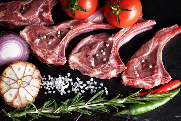 Costole dell'agnello del montone della carne cruda con le erbe sulla pietra nera con le spezie e gli ortaggi freschi