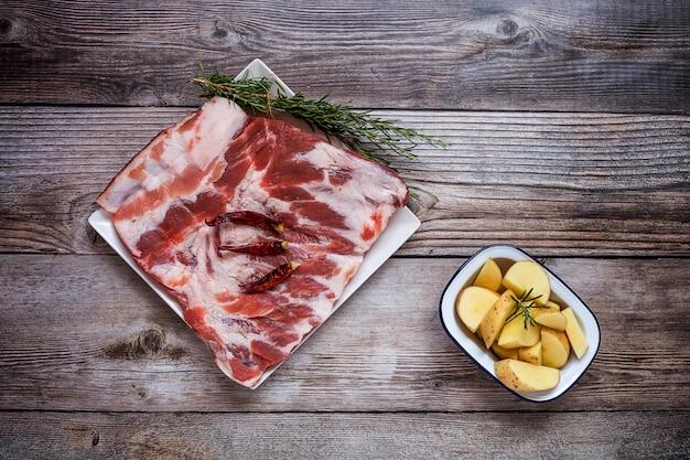 Costole di maiale crudo con erbe e spezie pronte per la cottura