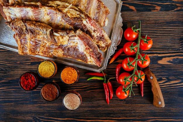 Costole di maiale marinate crude e pomodori di aglio pepe su un bordo nero