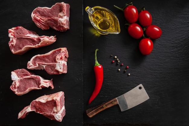 Costole e condimenti freschi crudi della carne di agnello su fondo di pietra nero