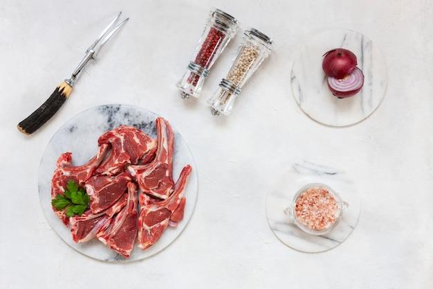 Costole e condimenti freschi crudi della carne di agnello su superficie bianca