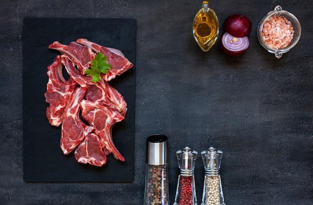 Costole e condimenti freschi crudi della carne di agnello su superficie scura