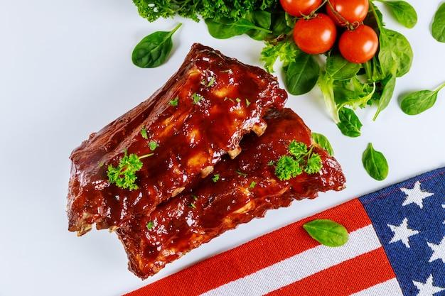 Costole posteriori del bambino del barbecue con le verdure e la bandiera americana.