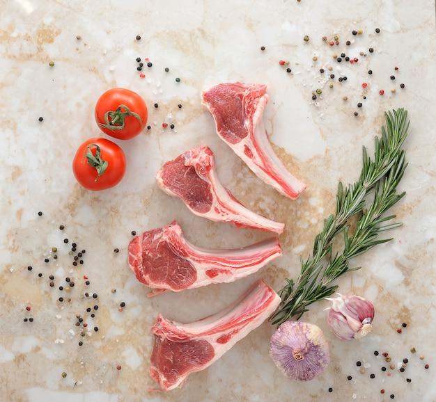 Costolette di agnello crude con rosmarino, aglio e pomodoro