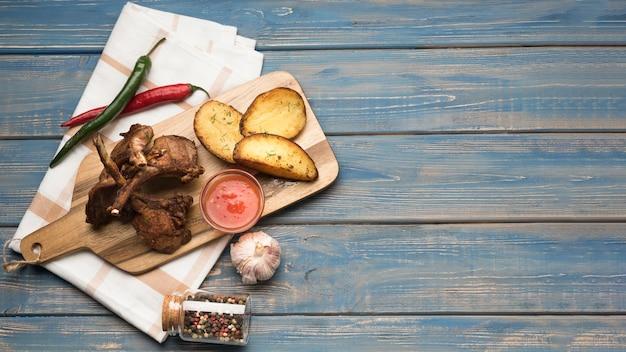Costolette di agnello distese su tavola di legno con patate e salsa con copia-spazio