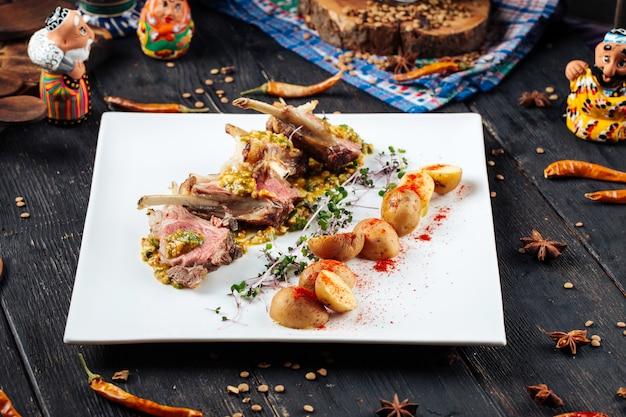 Costolette di agnello fritte gourmet con salsa e patate