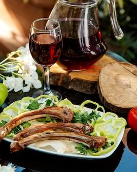 Costolette di agnello servite con peperone, cipolla, erbe e focaccia