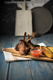 Costolette di agnello su tavola di legno con patate e salsa