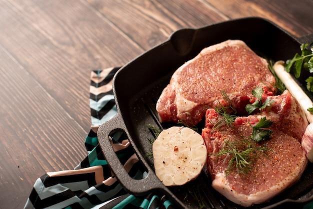 Costolette di carne di agnello crudo crudo con rosmarino e aglio in padella di ferro nero