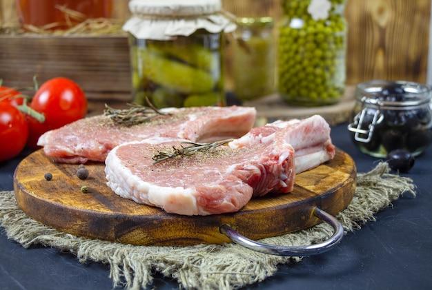 Costolette di filetto di maiale su un tagliere di legno.