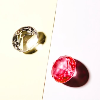 Costoso diamante bianco e rosso su sfondo bianco e beige