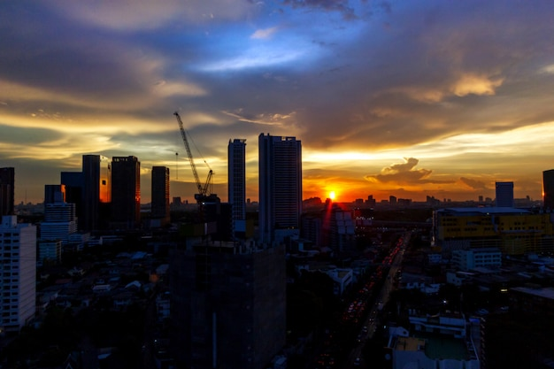 Costruendo al tramonto con il paesaggio della città del fondo di porpora del cielo blu blu crepuscolare