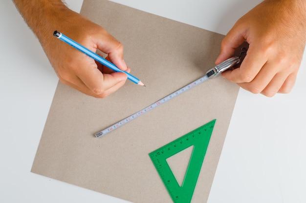 Costruire e riparare il concetto con la disposizione piana degli strumenti. mani che effettuano misurazioni