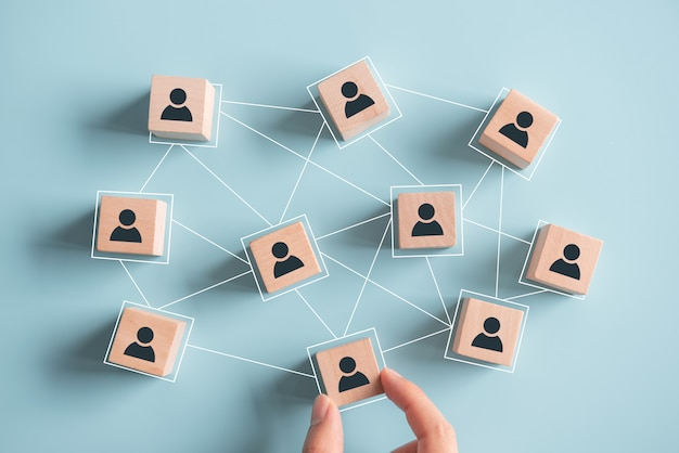 Costruire una squadra forte, blocchi di legno con icona di persone su sfondo blu, risorse umane e concetto di gestione.