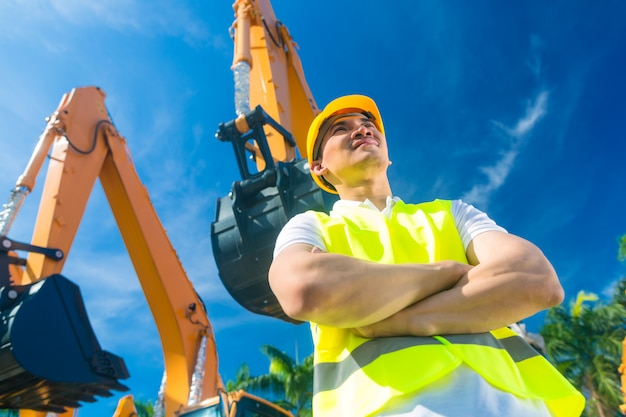Costruttore asiatico davanti all'escavatore della pala