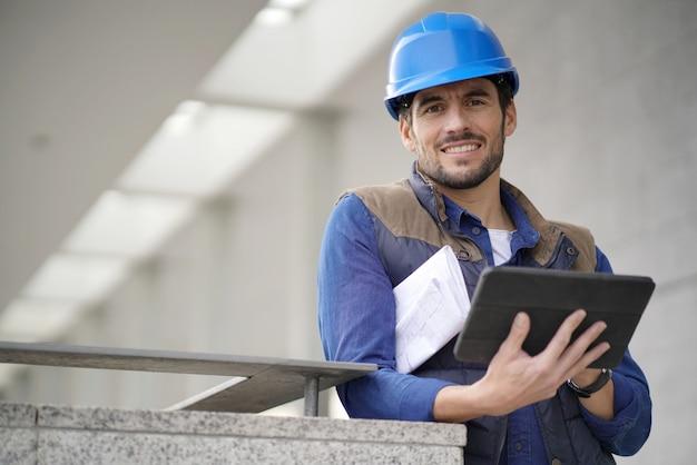 Costruttore attraente all'aperto con tablet e blueprints sorridendo alla telecamera
