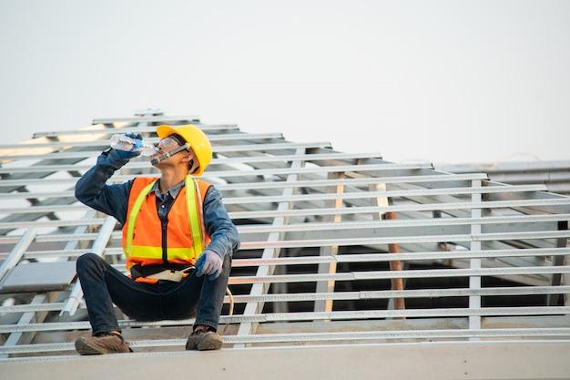 Costruttore che lavora al tetto di nuova costruzione, concetto di edificio residenziale in costruzione.