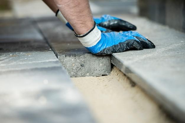 Costruttore che pone i nuovi mattoni della pavimentazione