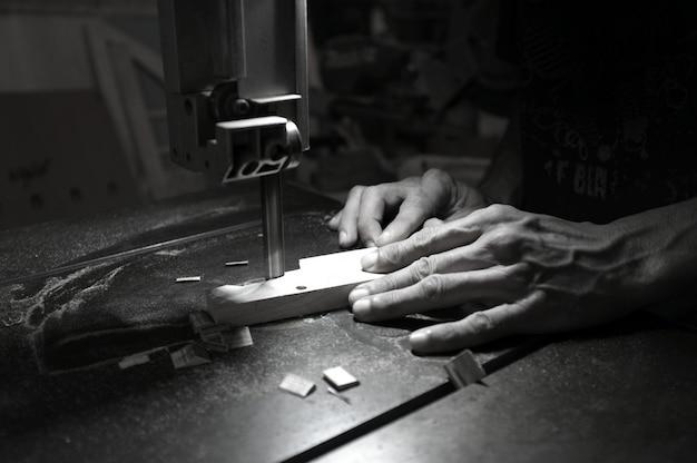 Costruttore del carpentiere che lavora con il puzzle e il legno elettrici. falegname che taglia un pezzo di legno