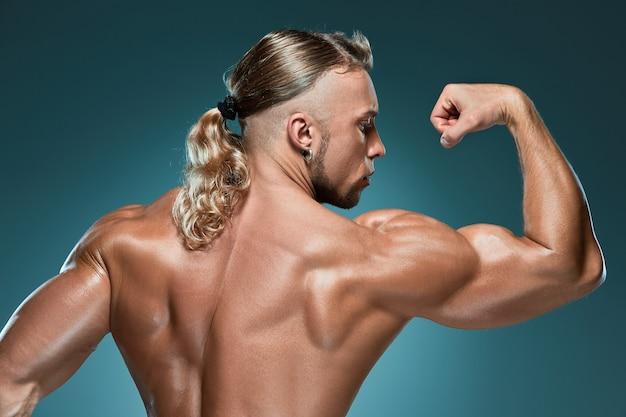 Costruttore di corpo maschio attraente su fondo blu