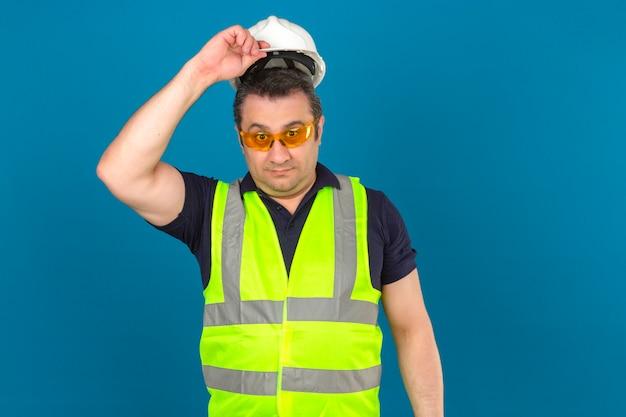 Costruttore di mezza età uomo che indossa maglia gialla costruzione e casco di sicurezza che sembra sorpreso decollando casco sopra la parete blu isolata