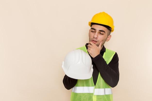 Costruttore maschio di vista frontale in casco giallo che tiene casco bianco pensando su sfondo chiaro