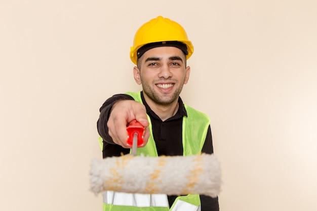 Costruttore maschio di vista frontale nel rullo giallo della tenuta del casco e che sorride sui precedenti crema
