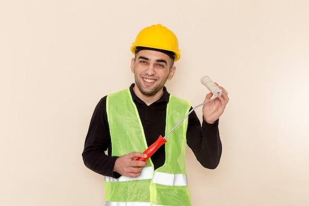 Costruttore maschio di vista frontale nel rullo giallo della tenuta del casco e che sorride sullo scrittorio crema