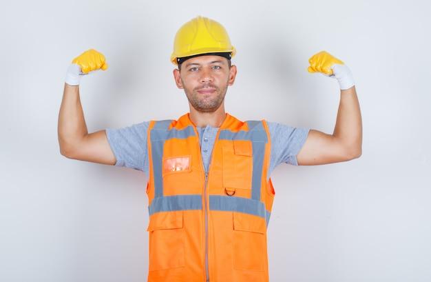 Costruttore maschio in uniforme che mostra il muscolo del braccio e sorridente e forte, vista frontale.