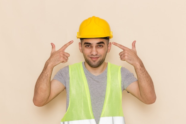 Costruttore maschio vista frontale in casco giallo in posa con espressione felice su sfondo chiaro