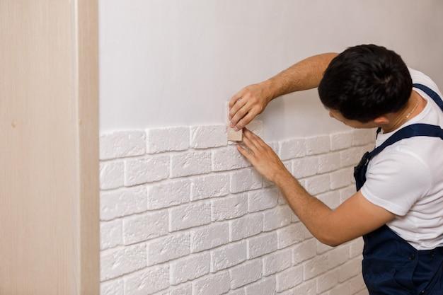 Costruttore professionista che incolla piastrelle decorative sulla parete. operaio monta mattoni decorativi sul muro