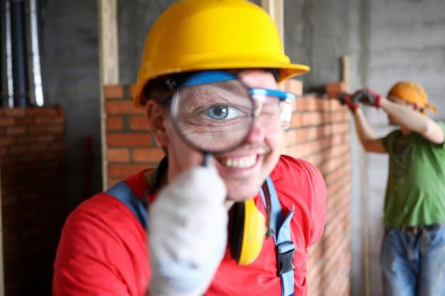 Costruttore sorridente in uniforme che esamina con attenzione lavoro finito