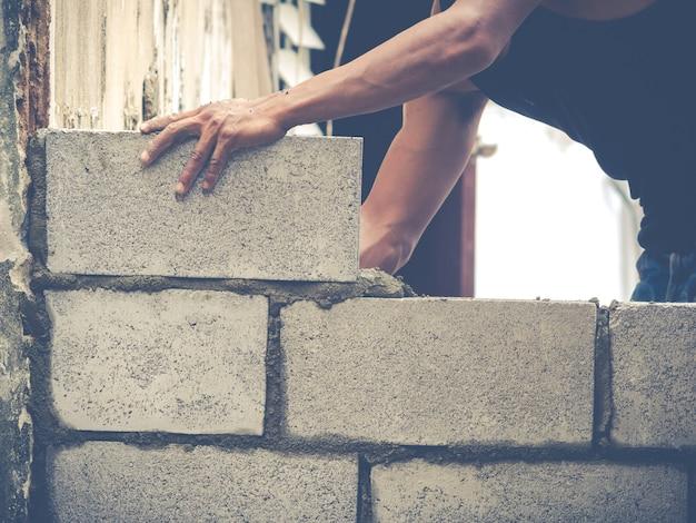 Costruttori di mattoni stanno costruendo muri