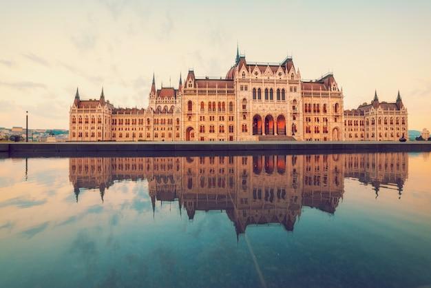 Costruzione del parlamento a budapest su un'alba con la riflessione