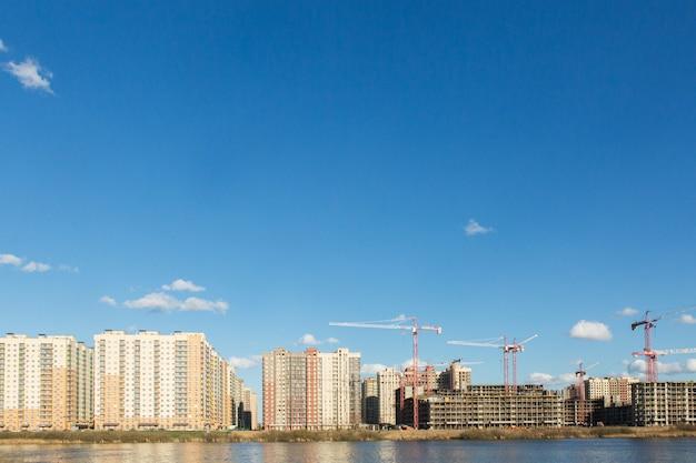 Costruzione di condomini, gru e cemento. panorama