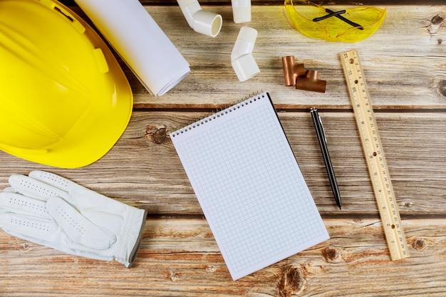 Costruzione di edifici su schemi con strumenti e casco su notebook con penna con attrezzature funzionanti