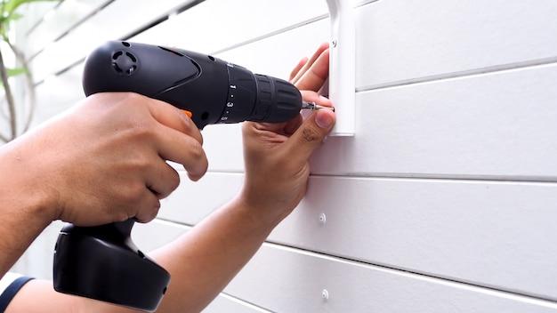 Costruzione di pareti di case, mediante perforazione di bulloni o viti inchiodate su piatto di legno bianco con trapani elettrici.