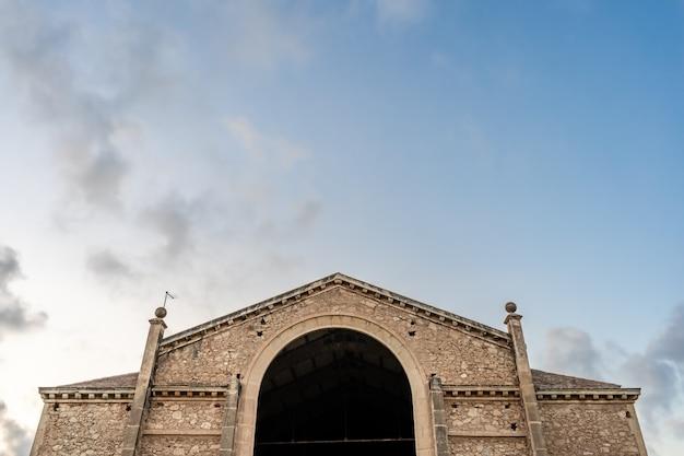 Costruzione di pietra rustica con il cielo blu nei precedenti