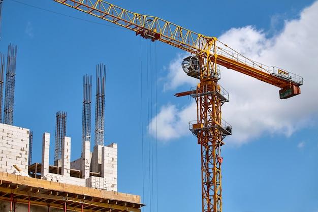 Costruzione di un grattacielo, formazione di supporti in cemento e funzionamento di una gru contro un cielo blu, messa a fuoco selettiva