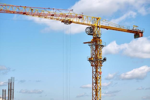 Costruzione di un grattacielo, operazione di una gru a torre contro un cielo blu, fuoco selettivo