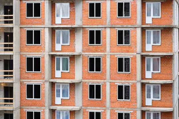 Costruzione di un nuovo edificio residenziale in mattoni con un inserto di finestre moderne in plastica.