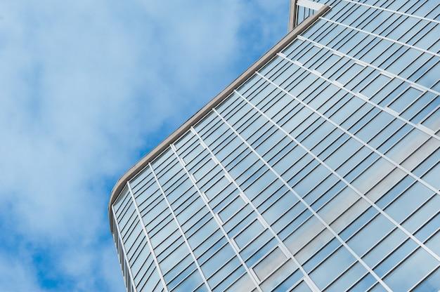 Costruzione di vetro del grattacielo contro il quadrato del fondo del cielo