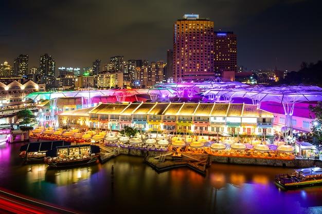 Costruzione leggera variopinta alla notte nel mercato di clarke quay con il fiume a singapore