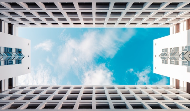 Costruzione moderna di architettura simmetrica con il cielo nuvoloso blu, fondo del grattacielo delle nuvole